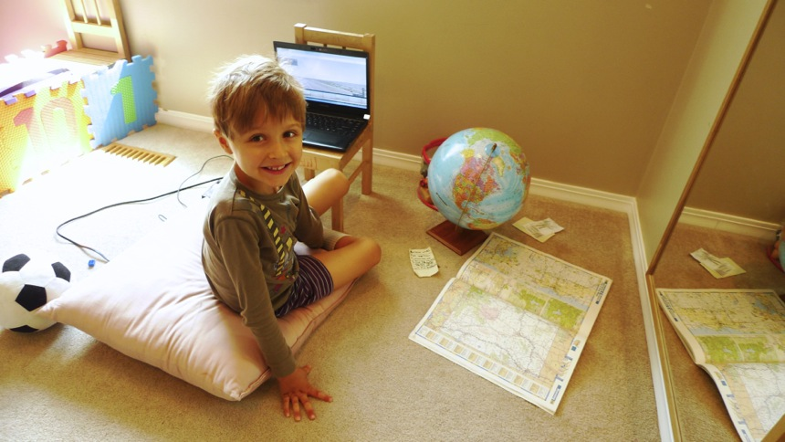 6-year-old boy smiling next to a laptop, an atlas, and a globe