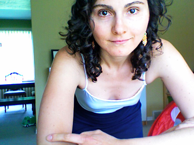 looking straight to camera with fresh curls, handmade amethyst earrings, a white tank and my new handmade ruched skirt