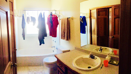 Bathroom before remodel with man's clothes hanging over the tub