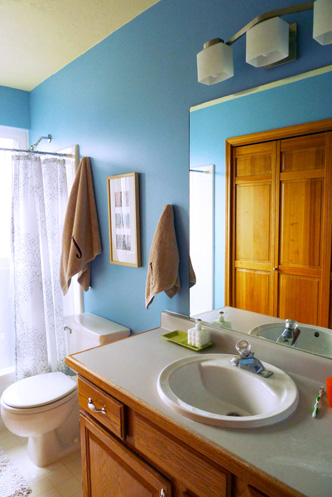 Remodeled bathroom showing the new blue walls, hung towels and finished shower curtain