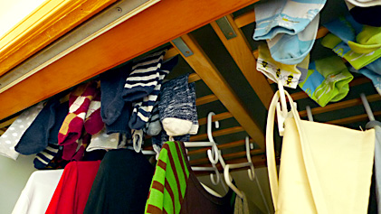 Closeup of clothes hanging on baby gate rails installed inside the laundry closet