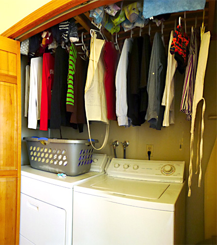 Clothes hanging on baby gate rails installed above laundry appliances