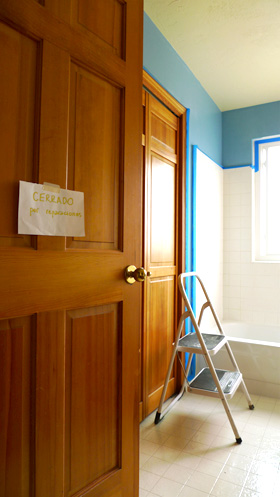 'Closed for reparations' sign on the wall of the freshly painted bathroom