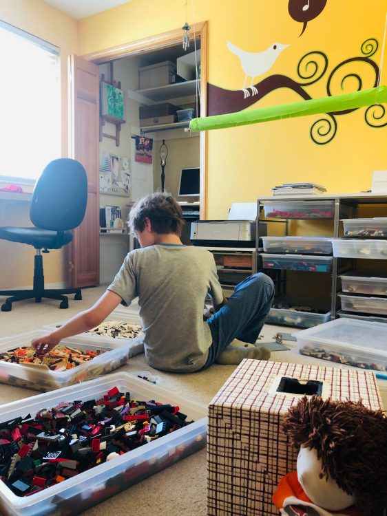 11.5-year-old working in the middle of several trays filled with lego bricks