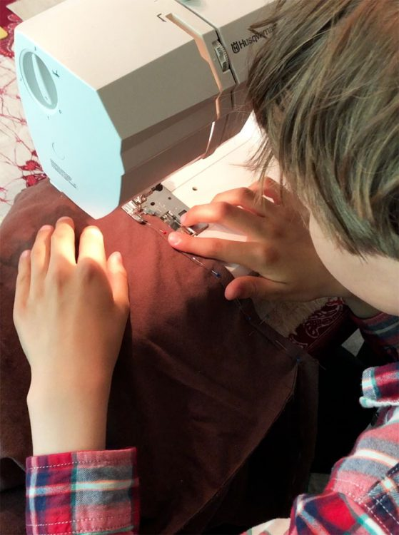 boy's hands carefully guiding fabric with pins through a sewing machine