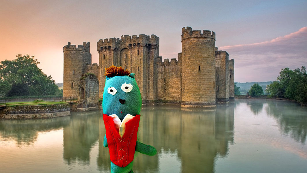 blue stuffed monster wearing a fancy vest in front of a castle