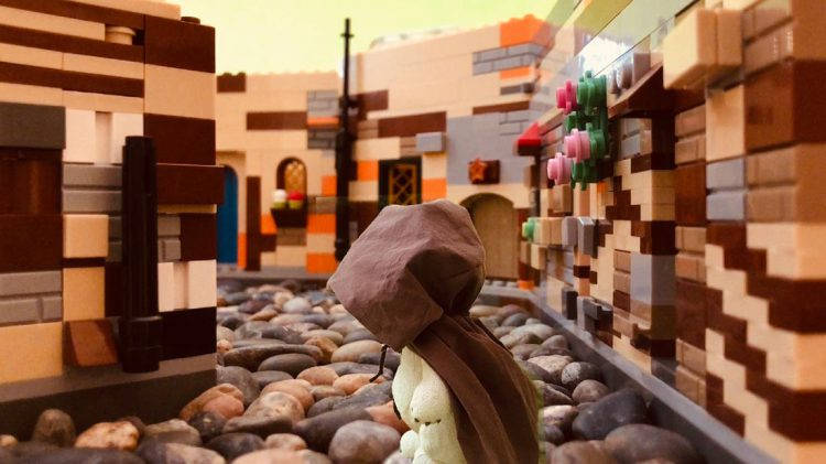 Composite image of a stuffed bear wearing a hooded cape in a street inside our lego set