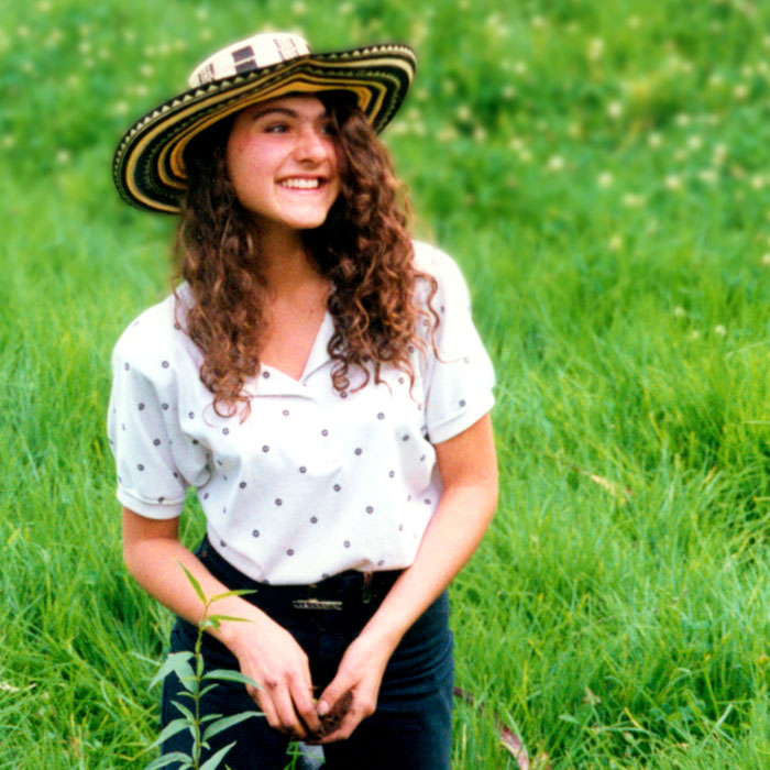 18-year-old Maria wearing a Colombian vueltiao hat while planting a fruit tree in a moor